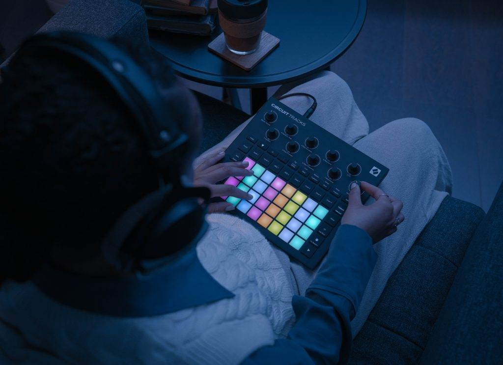 A lifestyle photo of someone demonstrating the portable aspect of the Novation Circuit Tracks groovebox.