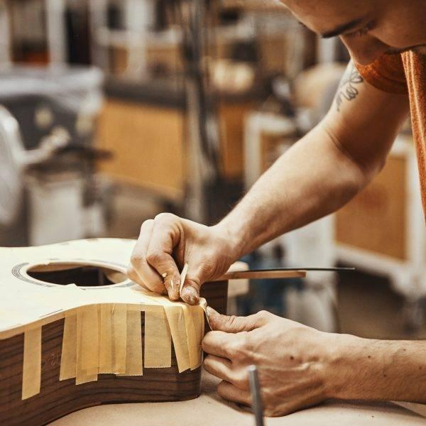 Taylor employee building a guitar